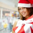 Young happy girl in Christmas hat. Standing indoors and holding — Stock Photo #7289365