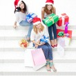 Stock Photo: Group of three beautiful girls sitting on stairs at shopping mal