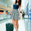 Young pretty stylish woman with luggage at the international air — Stock Photo