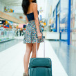 Young pretty stylish woman with luggage at the international air — Φωτογραφία Αρχείου