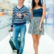 Portrait of young couple walking together at airport hall with t — Stock Photo #7289381