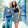 Portrait of young couple walking together at airport hall with t — Stock Photo #7289385