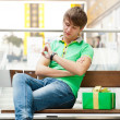 Portrait of young man inside shopping mall with gift box sitting — Stock Photo