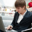 Portrait of handsome young man working with laptop at cafe at bu — Stock Photo