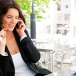 Portrait of young business woman sitting relaxed at outdoor cafe — Stock Photo