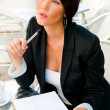 图库照片: Business woman working with documents while having lunch or brea