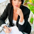 Stock fotografie: Business woman working with documents while having lunch or brea