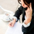 Closeup portrait of pretty woman sitting at cafe and signing doc — Stock Photo #7289482