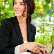 Portrait of a smiling young business woman using laptop at outdoor cafe, br — Stock Photo #7289500