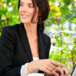 Portrait of a smiling young business woman using laptop at outdoor cafe, br — Stock Photo