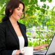 Portrait of a smiling young business woman using laptop at outdo — Stock Photo