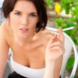 Portrait of a beautiful woman smokes a cigarette outdoor at cafe — Stock Photo #7289517
