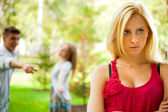 Upset teenage girl being jeered by group of the other young peop — Stock Photo