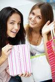 Two excited shopping woman resting on bench at shopping mall loo — Stock Photo