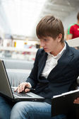 Portrait of handsome young man working with laptop at cafe at bu — Stockfoto
