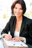 Närbild porträtt av vacker kvinna sitter på café och signering doc — Stockfoto
