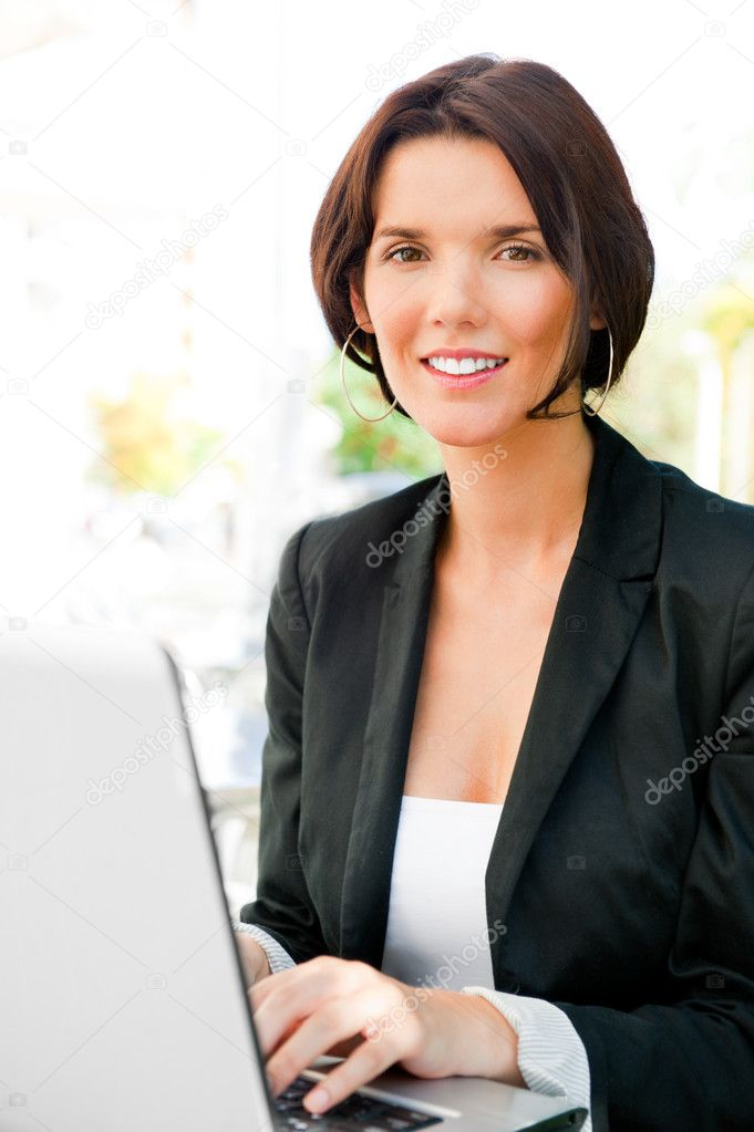 Young business woman on a laptop using wireless internet connection with 3g modem. Sitting outdoor at cafe on lunch time  Stock Photo #7289491