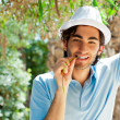 Young man wearing hat and casual clothes in sunny day. Leaning o — Stock Photo #7309646