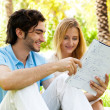 Happy couple of students with a notebook sitting on grass at cam — Stock Photo