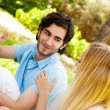 Happy couple of students with a notebook sitting on grass at cam — Stock Photo #7309653
