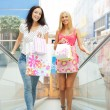 Closeup of two attractive happy girls out shopping. They are mov - Stockfoto