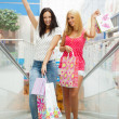 Closeup of two attractive happy girls out shopping. They are mov - Foto Stock