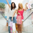 Closeup of two attractive happy girls out shopping. They are mov - Foto de Stock  