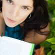 Beautiful girl sitting at park and reads the book. Looking up at — Stock Photo