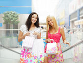Closeup of two attractive happy girls out shopping. They are mov — Foto Stock