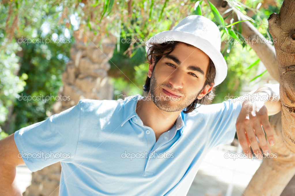 Young man wearing hat and casual clothes in sunny day. Leaning on palm tree at summer park — Stock Photo #7309647