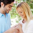 Happy young hispanic man gifting a ring to a beautiful surprised — Stock Photo