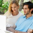 Young couple working on laptop and smiling while sitting relaxed — Stock Photo #7310159