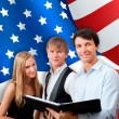 Stock Photo: Group of young students standing with their teacher against Amer