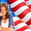 Portrait of a pretty young woman ôïôøòûå an American flag , smil — Zdjęcie stockowe #7557931