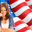 Portrait of a pretty young woman ôïôøòûå an American flag , smil — Stock Photo #7557931