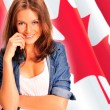 Stock Photo: Portrait of pretty young womagainst Canadiflag , smili