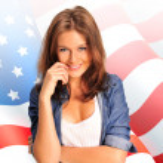 Portrait of a pretty young woman ôïôøòûå an American flag , smil — Stock Photo