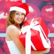 Young happy girl in Christmas hat. Standing indoors and holding — Stock Photo