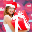 Young happy girl in Christmas hat. Standing indoors and holding — Stock Photo #7558083
