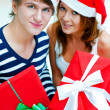 Young happy couple in Christmas hats standing together and holdi — Stock Photo #7558084