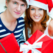 Young happy couple in Christmas hats standing together and holdi — Stock Photo #7558085