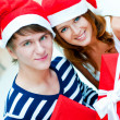 Young happy couple in Christmas hats standing together and holdi — Stock fotografie #7558087