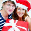 Foto Stock: Young happy couple in Christmas hats standing together and holdi