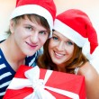 Stock Photo: Young happy couple in Christmas hats standing together and holdi