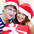 Young happy couple in Christmas hats standing together and holdi — Stock Photo #7558090