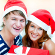 Young happy couple in Christmas hats standing together and holdi — Stock fotografie #7558091