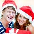 Young happy couple in Christmas hats standing together and holdi — Stock Photo