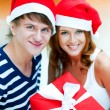 Young happy couple in Christmas hats standing together and holdi — Stock Photo #7558092