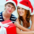 Young happy couple in Christmas hats standing together and holdi — Stock fotografie #7558097