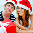 Young happy couple in Christmas hats standing together and holdi — 图库照片 #7558097